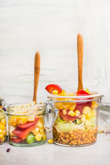Corn and lentil salads in glass jars on white wooden background. Healthy lifestyle or diet food concept