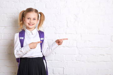 Cute smiling schoolgirl in uniform standing on light  background and showing  thumbs to the side. Copy space