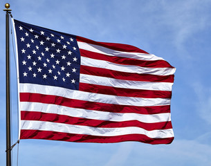 Flag USA waving in wind with blue sky and clouds