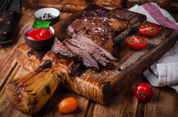 Sliced medium rare grilled Beef steak  with spices and ketchup  on cutting board on wooden background