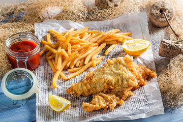 Closeup of tasty fish and chips in newspaper