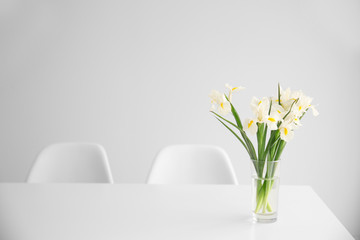 Beautiful white iris flowers on dinning table against white wall background