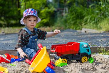baby plays in sandbox