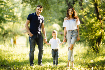 Father, mother and son walking in the garden