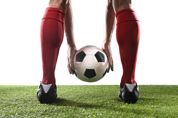 legs of football player in red socks and black shoes holding the ball in his hands placing free kick