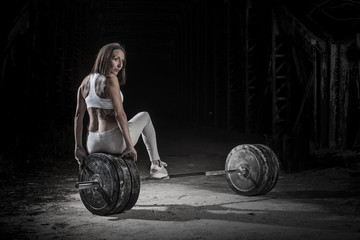 Woman working out with weights in the gym