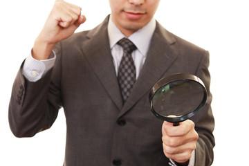 拡大鏡を持つビジネスマン