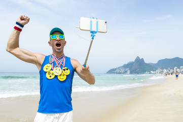 Athlete taking selfie wearing gold medals with bright yellow emoji faces with smartphone on selfie stick on Ipanema Beach in Rio de Janeiro, Brazil