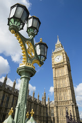 Big Ben shines in bright morning sun behind a decorative lamppost at Westminster Palace London