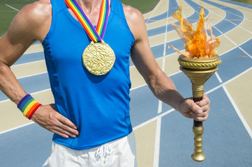 Gold medal athlete with gay pride rainbow ribbon holding ceremonial sport torch with inspirational flame in front of running track
