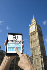 UK EU Referendum voter choosing between Remain and Leave on a digital tablet computer outside Big Ben Westminster Palace, London