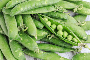 Green fresh peas on a wooden background