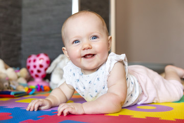 Smiling baby girl with blue eyes playing on floor