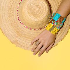 Bright stylish bracelets and straw hat. Go to the beach. Fashion