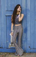 Hippie girl in front of bright blue door