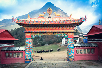 Gate Tengboche monastery in Nepal with the sacred wheel of Dharma and deer on them