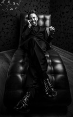 Handsome young man in dark suit relaxing on luxury sofa. Black-white photo.
