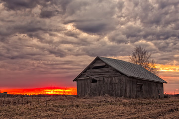 Sun Sets Behind An Old Barn House Wall mural