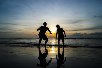 boys jumping on the beach Sunset