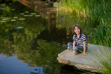 Smiling boy sitting on the edge of the pond