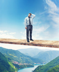 Man on the bridge above the mountain river