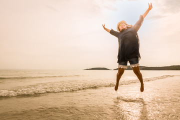 Happy young woman jumping on beach (tone color photo)