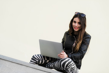 Beautiful student woman is smiling using a laptop and sitting on old wall in the university campus. Gorgeous girl working with computer outdoors at college park.