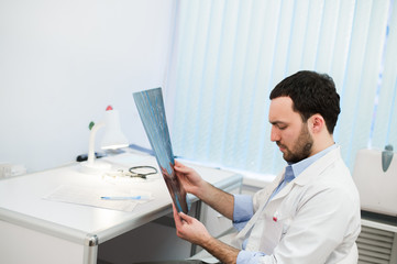 Young caucasian man doctor examines MRI image of human head in office