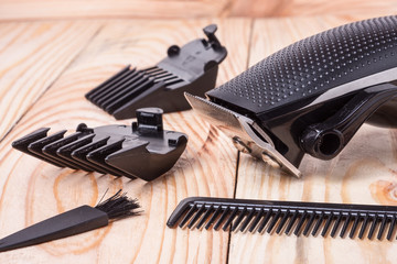 hair trimmer with attachment  and a comb on wooden background