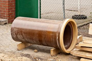 Ein grosses Abwasserrohr aus Ton liegt bereit zur Montage