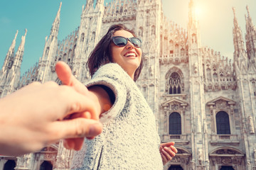 Smiling woman hold his boyfriend hand on Duomo di Milano backgro
