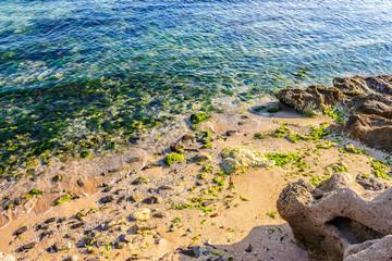 wave rolls onto the rocks of sandy coast