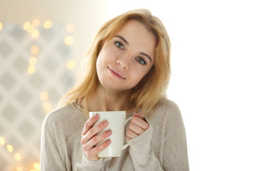 Blonde beautiful smiling girl wearing white shirt with opened eyes enjoying her cup of hot delicious coffee or tea on the light background