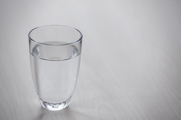 Glass of pure water on light wooden table