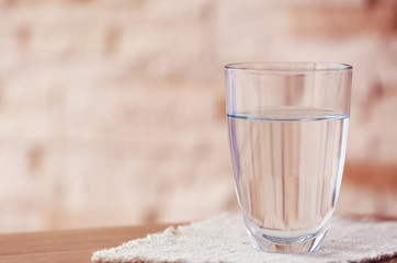 Glass of pure water with napkin on wooden table