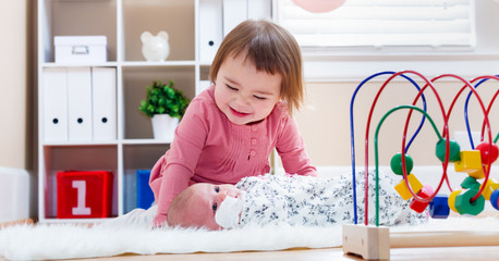 Happy toddler girl playing with her baby sibling