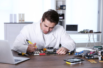 Man in white coat repairing electronic circuits in service center
