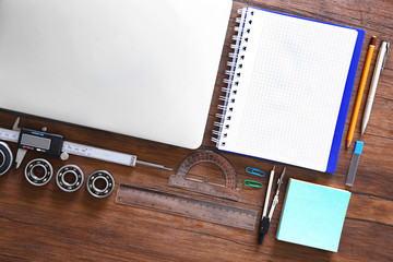 Laptop, notebook and engineering tools on wooden table, top view