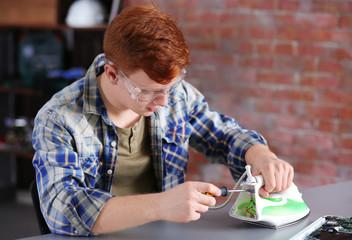 Young man fixing an iron in repair center