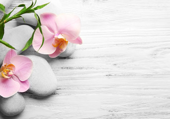 Spa stones, bamboo stack and orchid flowers on wooden background