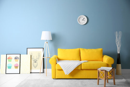 Room interior with yellow sofa on blue wall background