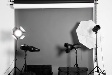 Empty photo studio with lighting equipment,  bags and backdrop