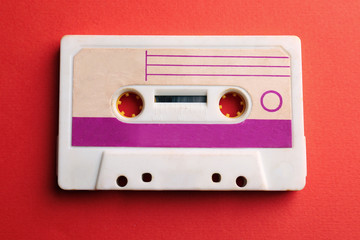Old audio cassette on red background