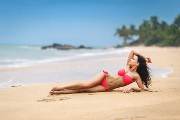 Beautiful girl in a sexy pink bikini on the beach