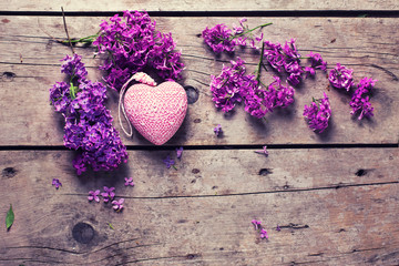 Fresh  violet lilac flowers and decorative pink  heart on aged