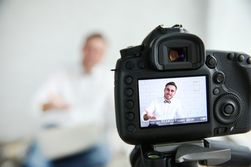 Young male blogger on camera screen