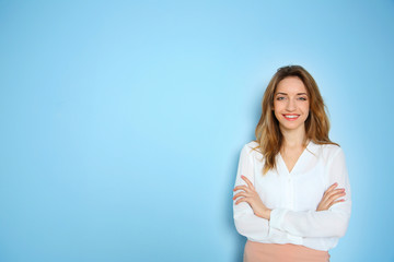 Portrait of young businesswoman against blue wall background