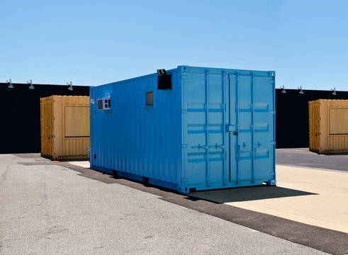 Blue and yellow mobile shipping containers in industriall site