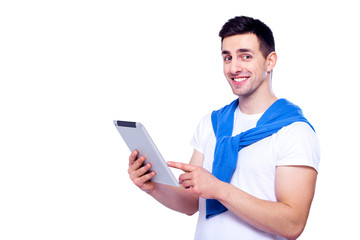 Smart technology makes everything easier. Confident young man in shirt working on digital tablet and smiling while standing against white isolated background