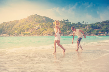 beautiful young couple walking along the shore of a tropical sea